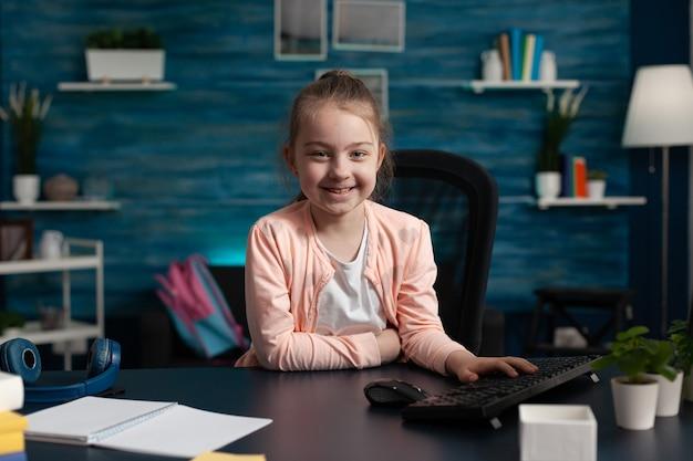 Retrato de uma criança da escola primária sentada na mesa de casa