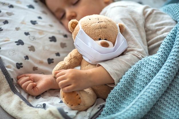 Retrato de uma criança dormindo e ursinho usando máscaras de ar. criança em quarentena em casa dormindo.