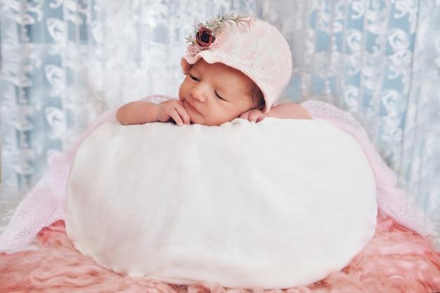 Retrato de uma criança dormindo em um boné com uma flor