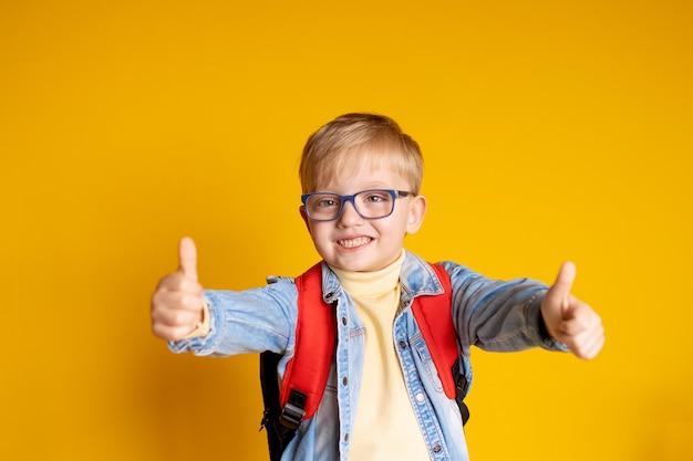 Retrato de uma criança feliz 5-6 anos de idade em uma parede amarela com livros e uma mochila, educação infantil.
