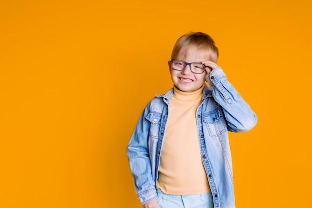 Retrato de uma criança feliz 5-6 anos de idade em uma parede amarela, criança com óculos