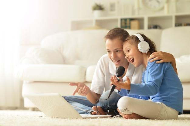 Retrato de uma criança feliz com o laptop em casa