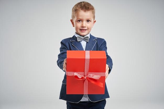Retrato de uma criança feliz e fofa segurando uma caixa de presente e olhando para a câmera isolada sobre fundo cinza