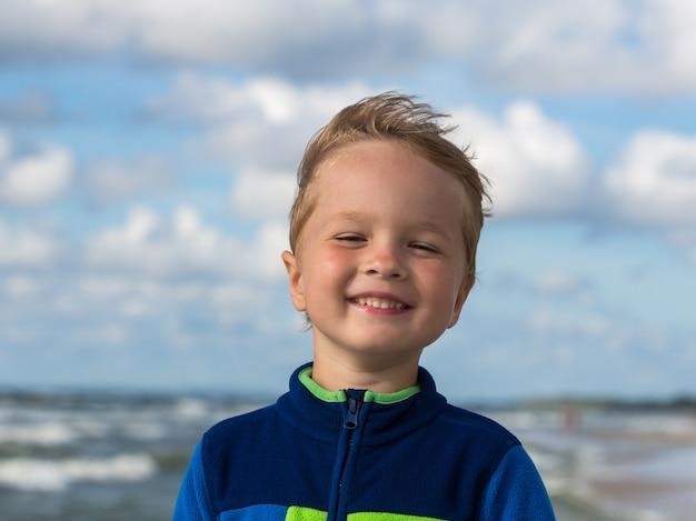 Retrato de uma criança feliz e sorridente no mar báltico