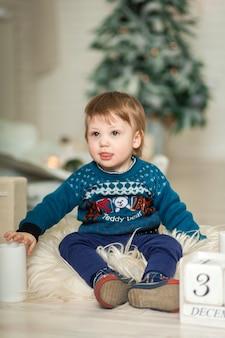 Retrato de uma criança fofa brincando no chão perto de uma árvore de natal.