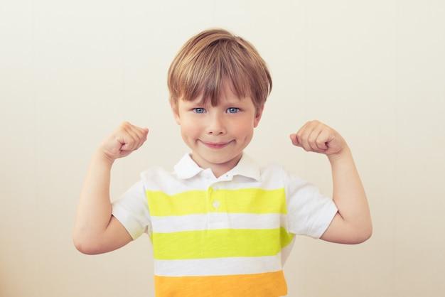 Retrato de uma criança forte mostrando os músculos dos braços em fundo branco