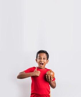 Retrato de uma criança indiana asiática alegre fofa segurando o cofrinho com livros e olhando para a câmera, isolada sobre fundo branco