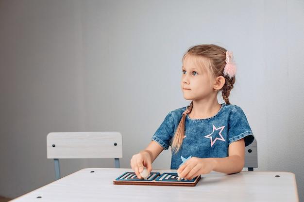 Retrato de uma criança linda e brilhante pensativa, sentada a uma mesa branca e resolvendo um quebra-cabeça para o desenvolvimento do pensamento e da lógica. conceito de brainstorming. foto com ruído