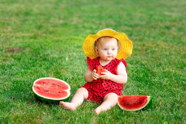 Retrato de uma criança no verão na grama verde comendo uma melancia com um chapéu amarelo, espaço para texto