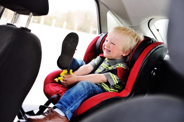 Retrato de uma criança nova de um menino com cabelo louro em um banco de carro das crianças.