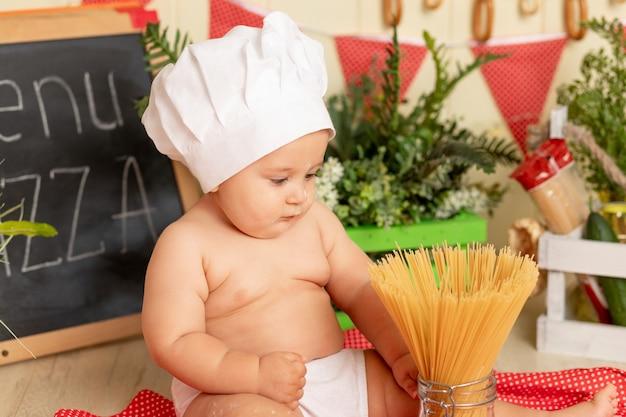 Retrato de uma criança pequena com um chapéu de chef preparando espaguete na cozinha