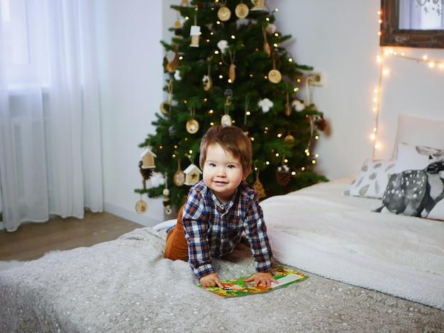 Retrato de uma criança perto da decoração de ano novo e de uma árvore