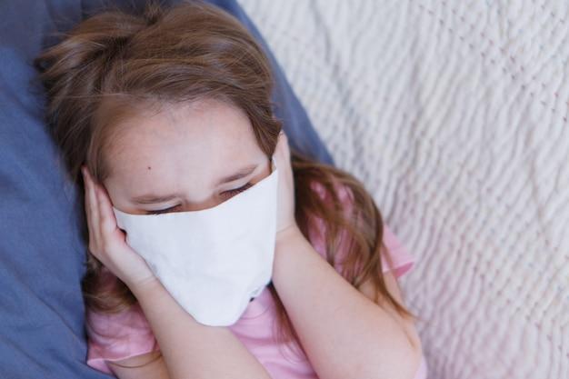 Retrato de uma criança que cobriu o rosto com uma máscara.