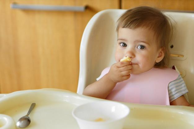 Retrato de uma criança que come comida de bebê com as mãos