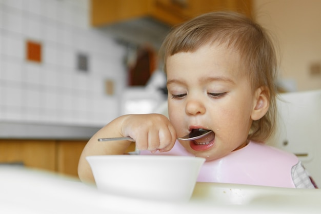 Retrato de uma criança que come comida para bebê com sua colher.