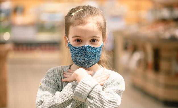 Retrato de uma criança usando uma máscara reutilizável em um supermercado durante a pandemia cobiçosa.