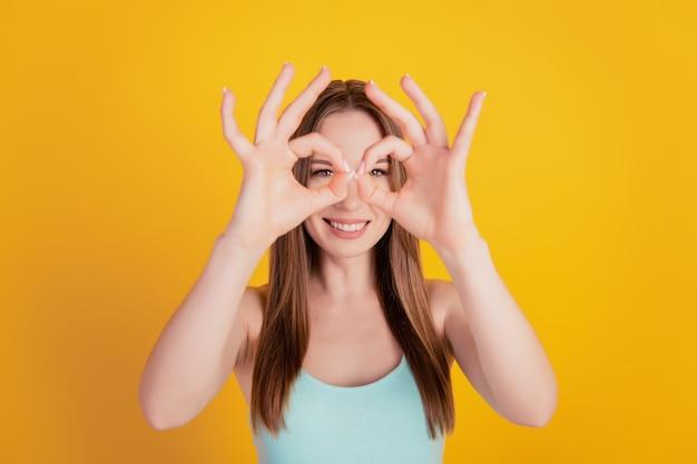 Retrato de uma dama infantil louca engraçada dois gestos ok cobrem os olhos brincando no fundo amarelo