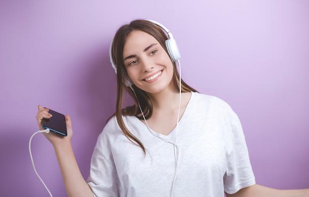 Retrato de uma dança de sorriso nova da mulher que escuta a música nos fones de ouvido de um smartphone.