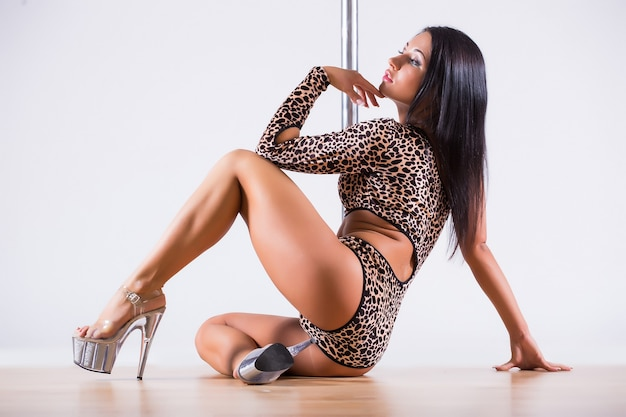 Retrato de uma dançarina feminina flexível, equilibrando-se no poste. isolado em fundo branco