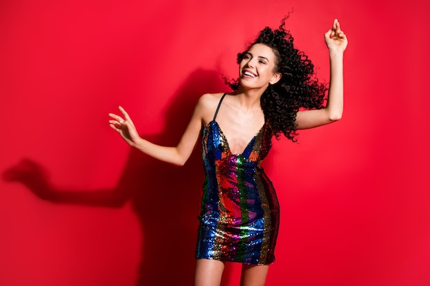 Retrato de uma deslumbrante alegre alegre garota de cabelos ondulados dançando e se divertindo baile isolado sobre um fundo de cor vermelha brilhante