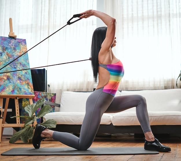 Retrato de uma desportista de meia-idade e bonita, com cabelos pretos e elásticos, fazendo alguns exercícios no tapete em casa.