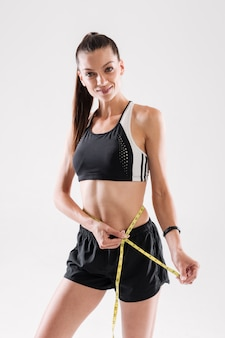 Retrato de uma desportista feliz medindo a cintura dela