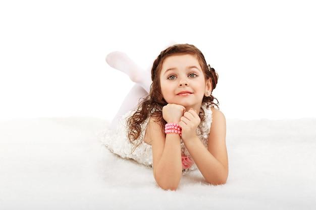 Retrato de uma divertida menina da moda deitada sobre um tapete fofo no chão contra o branco