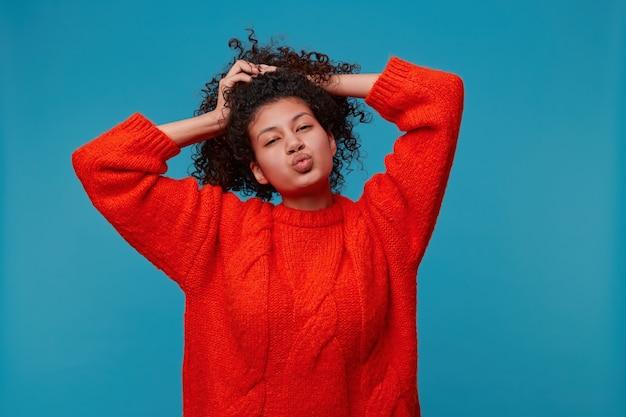 Retrato de uma doce mulher em um suéter vermelho com um rosto brincalhão e flertando segurando seu adorável cabelo preto encaracolado