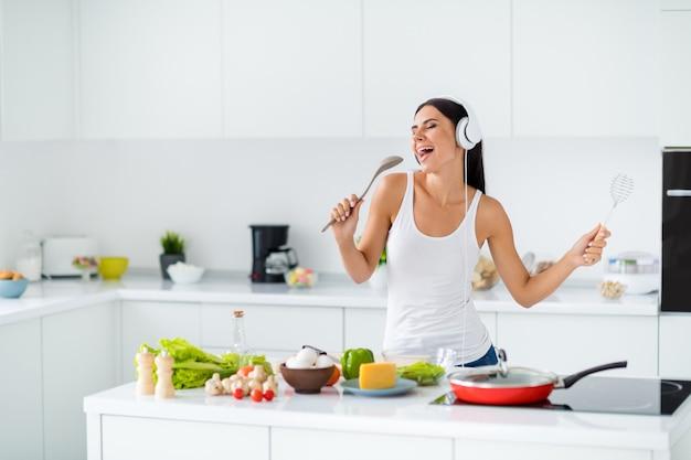 Retrato de uma dona de casa alegre e descolada imagina que ela pop começa a ouvir música em seu fone de ouvido segurar o utensílio de cozinha e canta a música favorita enquanto cozinha o jantar saboroso almoço na casa branca