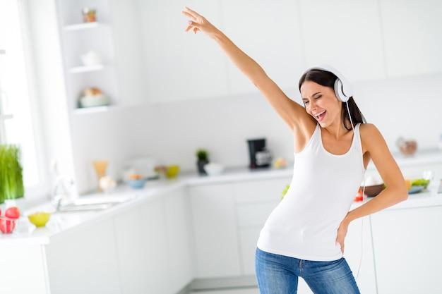 Retrato de uma dona de casa alegre e descolada quer relaxar depois de cozinhar, usar fone de ouvido, dançar, ouvir música, melodia alta, sentir como um moderno vestido de camiseta branca na cozinha branca