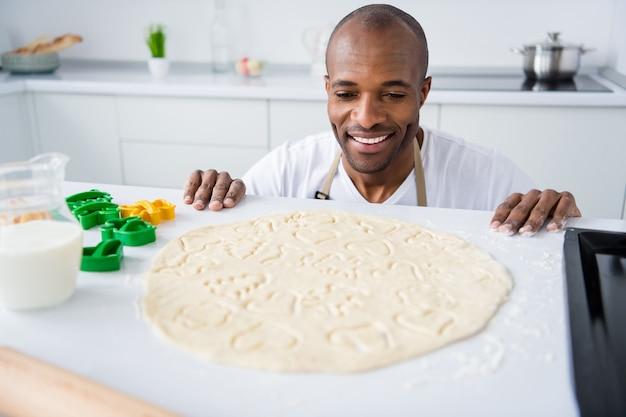 Retrato de uma dona de casa atraente fazendo bolo de torta de lanche feito à mão usando a forma na cozinha branca