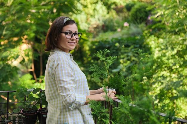 Retrato de uma dona de casa madura, feminina, com uma xícara de café na varanda aberta decorada com plantas verdes, copie o espaço