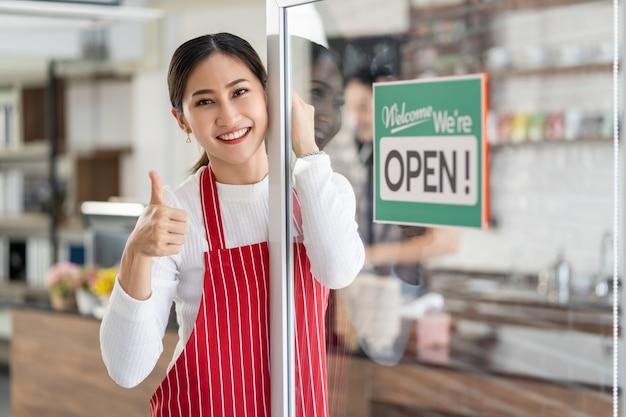 Retrato de uma dona de pé no portão de sua cafeteria