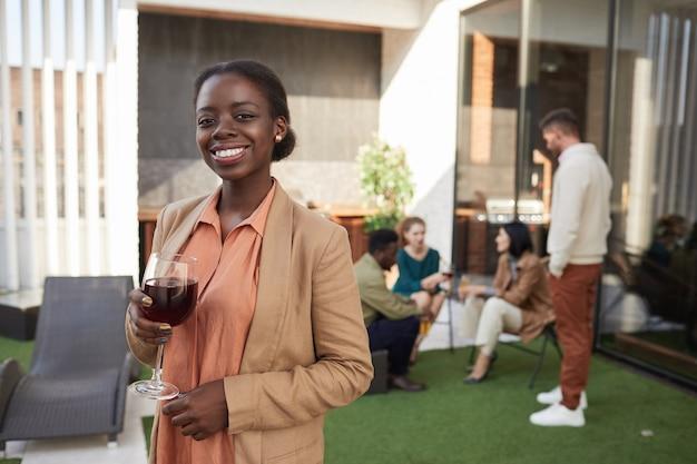Retrato de uma elegante mulher afro-americana segurando a taça de vinho da cintura para cima enquanto desfruta da festa ao ar livre.