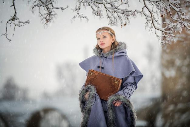 Retrato de uma elfa com um grande livro nas mãos no contexto da natureza de inverno e uma antiga fortaleza