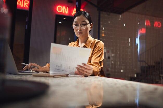 Retrato de uma empresária asiática lendo documento enquanto trabalha até tarde no escritório escuro