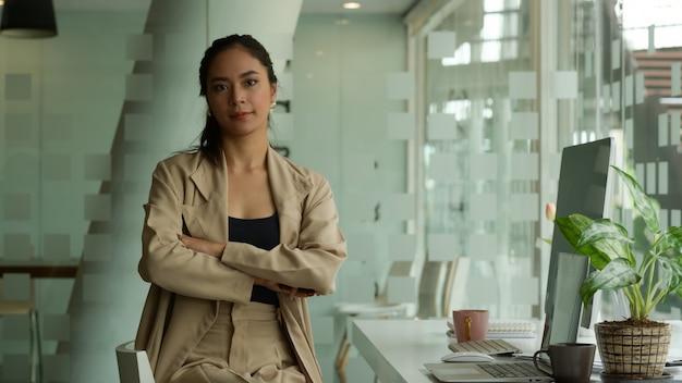Retrato de uma empresária de braços cruzados e sorrindo enquanto está sentada na sala de um escritório com parede de vidro