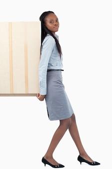 Retrato de uma empresária empurrando um painel com as costas