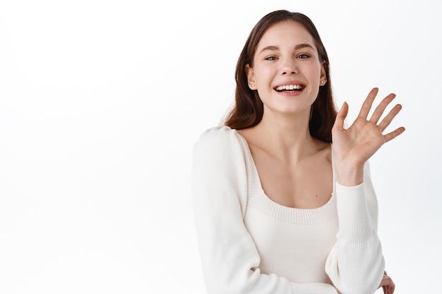 Retrato de uma empresária europeia despreocupada e amigável, segurando a mão no peito e sorrindo amplamente enquanto acenava com a palma da mão levantada, cumprimentando um amigo, encontrando-se com colegas de trabalho em um café