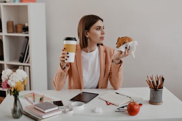Retrato de uma empresária na hora do almoço no escritório. trabalhador comendo hambúrguer no local de trabalho.