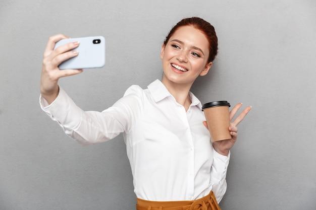 Retrato de uma empresária ruiva caucasiana tirando uma foto de selfie em um smartphone no escritório e bebendo café para viagem em um copo plástico isolado sobre cinza