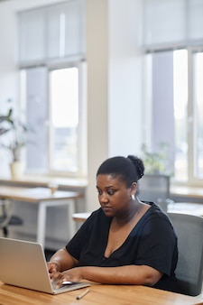 Retrato de uma empresária séria trabalhando em um laptop na mesa de um escritório moderno, preenchendo formulários online