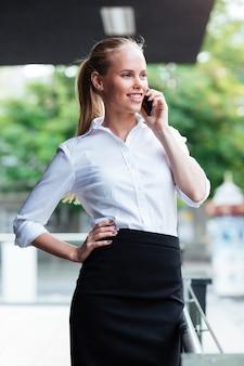 Retrato de uma empresária sorridente, falando ao telefone e olhando para longe ao ar livre