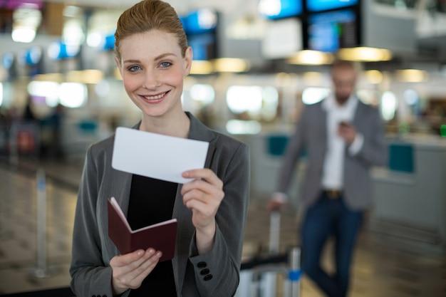 Retrato de uma empresária sorridente, mostrando seu cartão de embarque