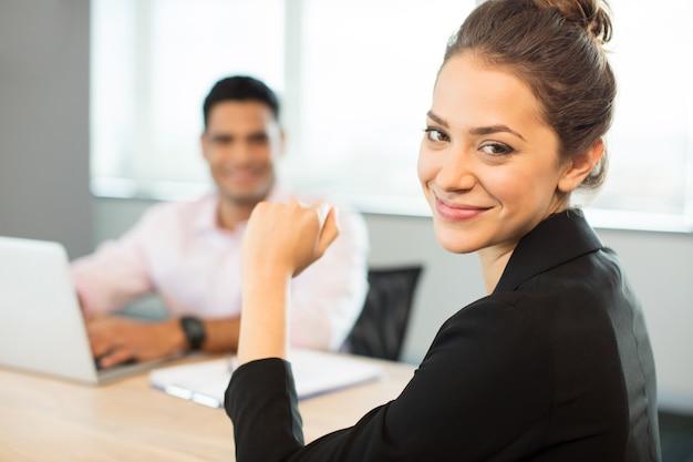 Retrato de uma empresária sorridente, sentada à mesa
