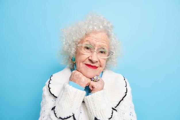 Retrato de uma encantadora aposentada de cabelos grisalhos mantém as mãos embaixo do queixo parece com expressão satisfeita, ouve palavras agradáveis sendo feliz usa um macacão