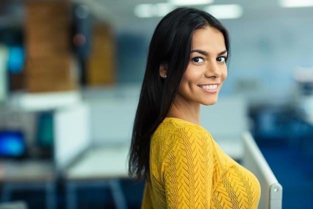 Retrato de uma encantadora empresária sorridente em pé no escritório ao ar livre