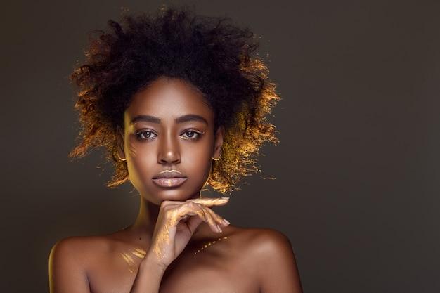 Retrato de uma encantadora garota africana com cabelo preto cacheado e padrões de tinta dourada