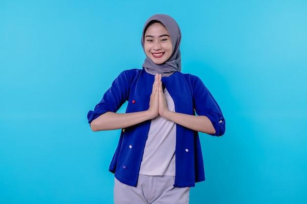 Retrato de uma encantadora garota boba glamour usando um hijab de mãos dadas perto do peito e sorrindo amplamente