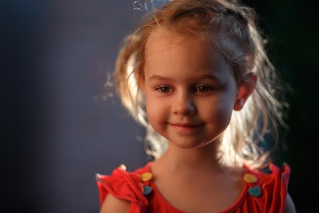 Retrato de uma encantadora garota loira do lado de fora em uma noite quente de verão, o sol ilumina o cabelo por trás.